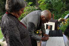 ANC stalwart Ahmed Kathrada and former Minister Barbara Hogan sign the registry book at the former South African President Nelson Mandela's house in Houghton, Johannesburg